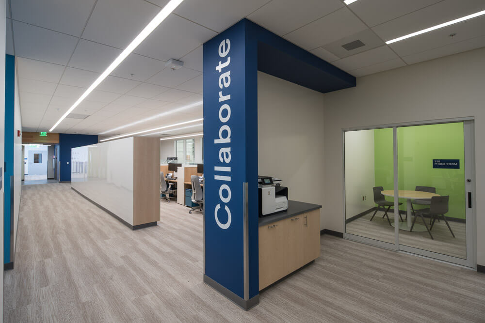 Interior photo of offices at Alaska Airlines Maintenance & Operations Facility with Collaborate written on the wall.