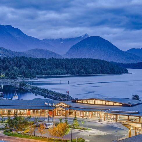 Exterior view of the Harrigan Centennial Hall with mountains of Sitka behind.